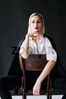 Fashion portrait of sensual trendy woman posing on retro chair against black studio background.