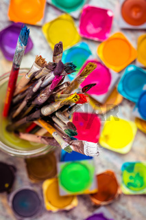 Set of colorful watercolor paints and paintbrushes for painting closeup. Selective focus.