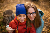 Autumn portrait of happy beautiful woman with her son
