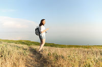 Side view of carefree female standing near sea and at sundown