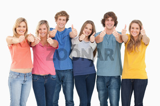 Six friends giving thumbs up as they smile