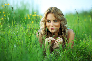blonde lays on green grass