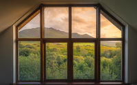 View through the window on beautiful sunrise over Carrauntoohil mountain and MacGillycuddys Reeks mountains