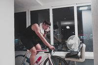 Man cycling on the machine trainer he is exercising in the home at night playing online bike racing game