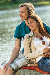 Smiling teen couple sitting on a rock