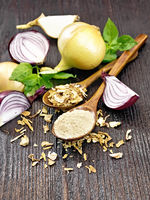 Onion powder and flakes in spoons on wooden board