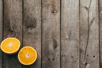 Sliced halves of orange fruit on gray wooden background. Pulp
