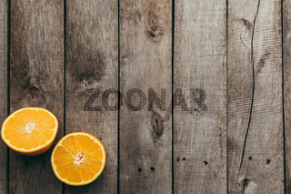 Sliced halves of orange fruit on gray wooden background. Pulp