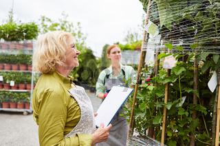 Gärtner im Gartencenter mit Checkliste bei der Inventur