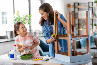 mother and daughter with ruler measuring old table