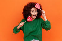 Positive satisfied woman with Afro hairstyle wearing green casual style sweater holding two heart shape lollipops, having fun, funny expressions.
