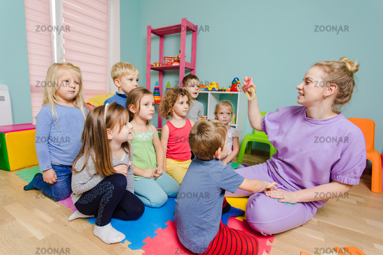 Lovely preschoolers listening young teacher very carefully