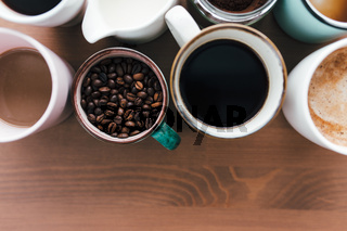 Multiple coffee cups, milk, beans and ground coffee in jar on wooden background