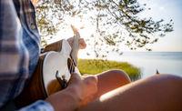 Woman at sunset playing the ukulele