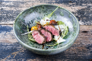 Modern Style Italian tagliata di manzo with dry aged sliced sirloin steak and lamb salad served as close-up in a design ceramic bowl