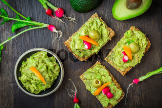 Wholemeal bread with avocado spread and vegetables on wooden kitchen table