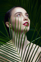 Romantic female with palm leaves on green background