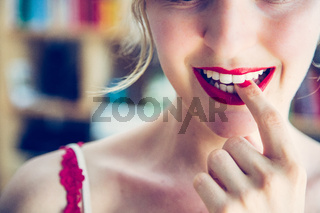 Attractive red lip stick: Blonde young woman with colorful nail polish is looking herself in the mirror. Cut out of the face.