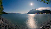 Mountain lake Walchensee with village Urfeld and Herzogstand in Bavaria, Germany at night with stars and full moon