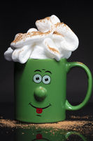 Funny green cup with a cheerful face with whipped cream. An invigorating drink in the morning.