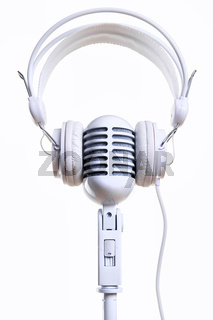 White vintage microphone and headphones over white background