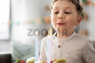 happy little boy blowing candles on birthday cake
