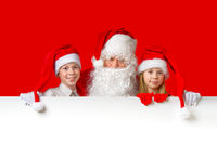 satna claus with funny children in red christmas gnome hats peeking out from behind a blank white banner