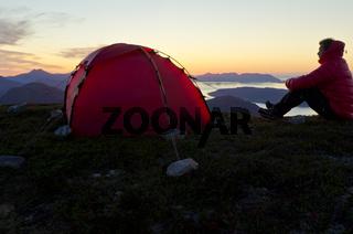 Wanderer sitzt auf einem Berggipfel neben seinem Zelt und sieht auf Moldefjord und Nordsee, Moere und Romsdal