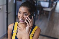Mixed race female creative worker talking on smartphone and smiling