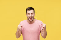 Young man celebrating with winner gesture on yellow background