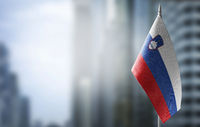 A small flag of Slovenia on the background of a blurred background