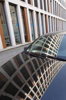 Fassade eines Bürogebäudes spiegelt sich in einem Auto