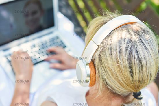 Freelancer Frau mit Kopfhörern am Laptop Computer