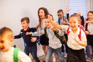 Happy school kids running in elementary school hallway, front view