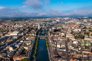 Establisher shot of Dublin skyline with river flowing with bridge connecting two sides of street surrounded by buildings during a cloudy day