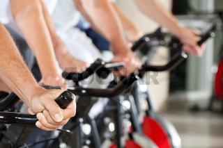 Hände an Spinning-Rädern im Fitnesscenter