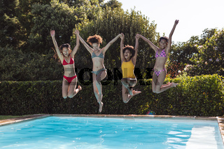 Diverse group of female friends having fun and jumping into water at a pool party