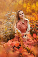 Beautiful young blonde woman in dress sitting with pensive look in tall grass in autumn forest
