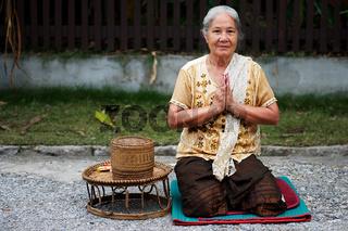 Frau aus Laos beim Gebet auf der Straße