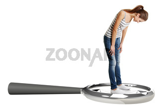 Teen student girl standing on giant loupe