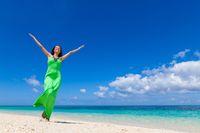 Woman in green dress on beach