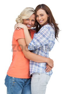 Two cute friends looking at the camera and hugging