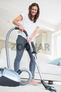 Woman holding vacuum cleaner smiling