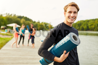Lächelnder junger Mann als Yoga Lehrer
