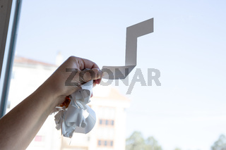 Close up of a Woman hand removing a vinyl sticker from a window with a tool
