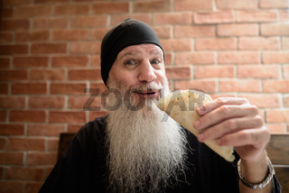 Man smiling with long gray beard while holding taco at restaurant