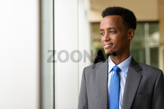 Portrait of handsome African businessman looking through window while thinking