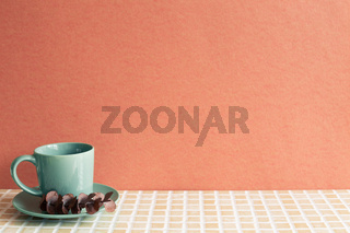 Mint coffee cup with eucalyptus leaf on mosaic tile table. red wall background