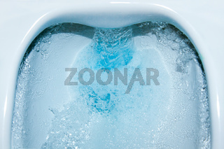 Water running down in drain. Toilet bowl flush with blue cleaning fluid. cleaning Toilet close-up.