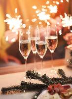 Blurred background of festive lights and elegant peoples hands holding xmas sparkles